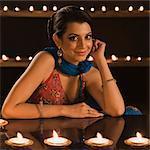 Woman smiling near oil lamps at Diwali festival