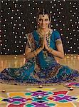 Woman greeting in prayer position near rangoli at Diwali festival