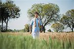 Farmer walking in the field, Sohna, Haryana, India