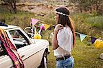 Croatia, Dalmatia, Young woman with headband looking at car