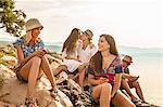 Croatia, Dalmatia, Young people at the seaside, using phones