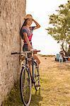 Croatia, Dalmatia, Young woman at the seaside, leaning against wall