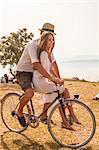 Croatia, Dalmatia, Young couple at the seaside, riding a bike
