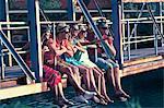 Croatia, Dalmatia, Young people sitting on footbridge, side by side