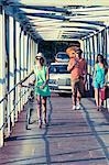 Croatia, Dalmatia, Young people walking along footbridge, cars in background
