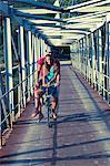 Croatia, Dalmatia, Young couple on footbridge, riding a bike