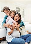 Family hugging in living room
