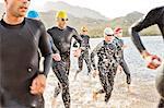 Triathletes in wetsuits walking in waves