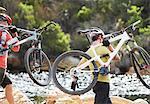 Men carrying mountain bikes in river