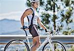 Man standing on bicycle on rural road