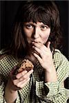 portrait of a poor beggar woman eating bread