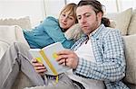 Couple On Sofa, Man Reading Book