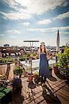 Young Woman On Balcony Holding Garden Rake, Munich, Bavaria, Germany, Europe