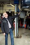 Happy senior man looking at car lifted on jack at auto repair shop