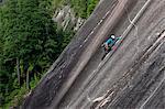 A climber scales cliffs at Squamish Chief, Squamish, British Columbia, Canada, North America