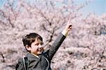 Young boy in school uniform between cherry trees