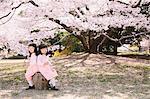 Female twins sitting under a cherry tree