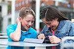 Girl and boy having fun on an iPad outside.