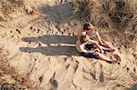 Two boys sitting on beach, high angle
