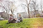 Two businesswomen sitting on grass in park