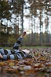 Boy lying on forest floor holding leaf in air