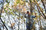 Boys up tree looking through binoculars