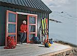 Woman outside chalet with skis, Klaengsholl, Skidadalur, Dalvik, Iceland