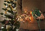 Mature male holding christmas tree lights