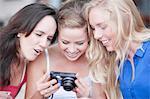 Three young women looking at photos