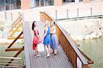 Three young women walking over bridge