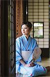 Japanese woman in a Yukata on tatami looking away