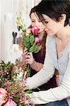 Mid adult woman and teenage girl choosing flowers in florists