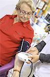 France, drugstore, pharmacist checking client's bloodpressure
