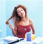Portrait woman untangling her hair in bathroom