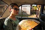 Woman in taxi holding fan