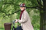 Senior woman riding bicycle in park, portrait