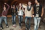 Five teenagers walking through tunnel laughing and joking