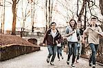 Five teenagers running through park