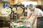 Baker inspecting packaging on bread rolls production line bakery