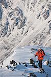 Female climber walking up snow covered ridge