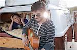 Mid adult man playing guitar at back of camper van, smiling