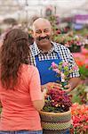 Mature man serving young woman in garden centre, portrait