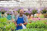 Mature gardener watering plants in garden centre, portrait
