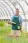 Mature man holding clipboard in garden centre, portrait
