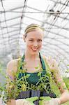Mid adult woman holding plants in garden centre, portrait