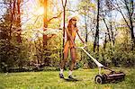 Woman wearing bikini mowing grass