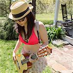 Woman wearing hat playing guitar