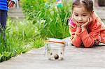 Young girl in garden watching jar of snails