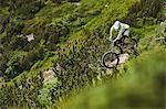 Mountain biker riding down steep hill path