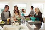 Three generation family in kitchen preparing food